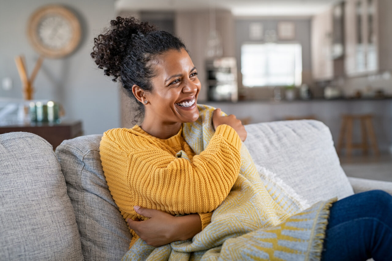 Joyful woman with blanket on couch smiling