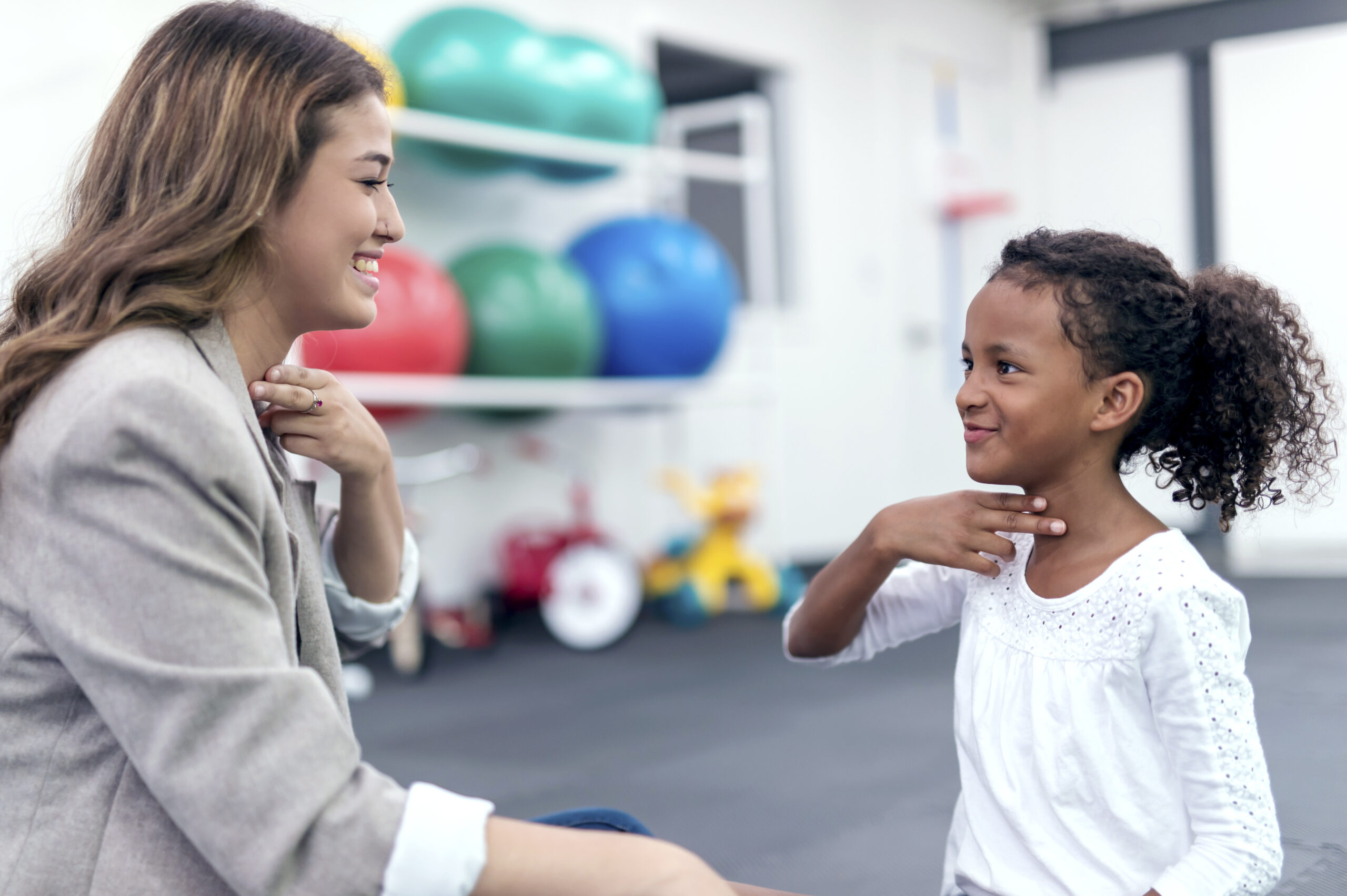 Female therapist helping girl in speech therapy exercise